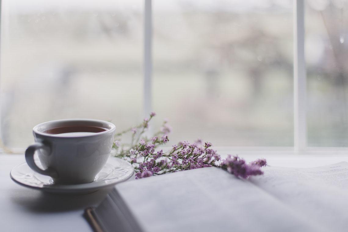 cup of tea, book, flowers in front of window - Simple Anti-Inflammatory Tea
